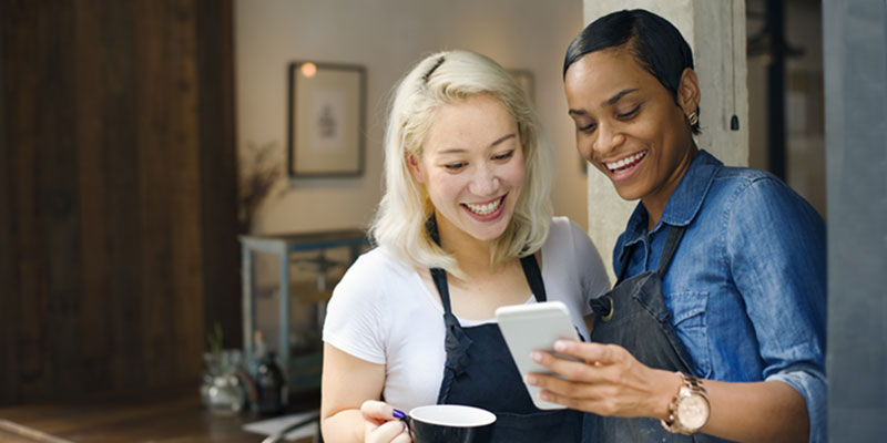 Two business ladies in aprons looking at a cell phone